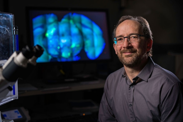 Man sitting near a microscope with blue images of a brain on a screen behind him