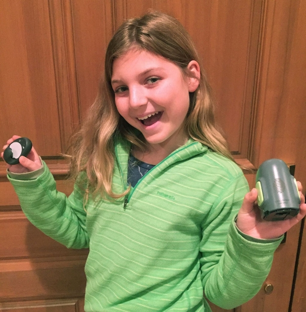 Young girl holding up parts of her closed-loop insulin delivery system