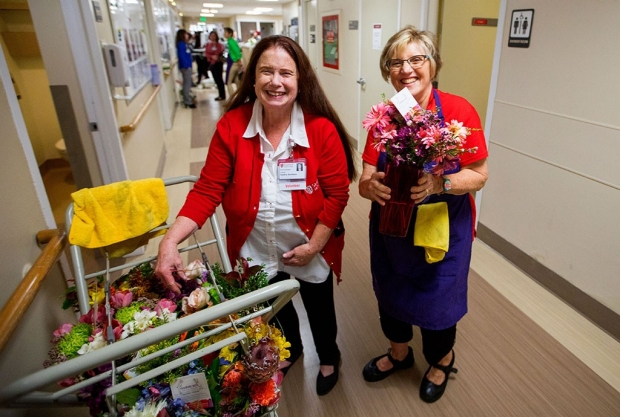 Two women carrying flowers in a hospital hallway