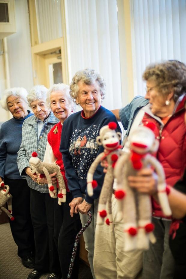 Five women holding sock monkeys they created