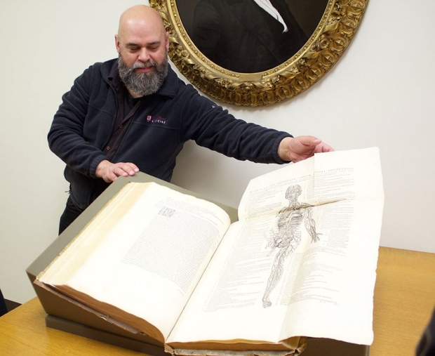 Man holding open a large, old book of anatomy illustrations