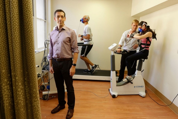 Man standing in a room where another man is running on a treadmill and a woman is on an exercise bike