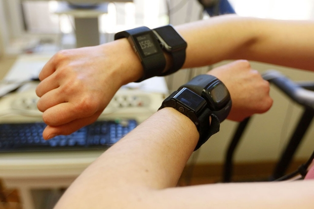 Two arms on which people are wearing a total of four fitness trackers