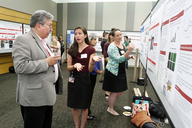 Students talking to faculty about their research posters