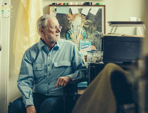 Man sitting at a desk at his home as he turns to look out a window