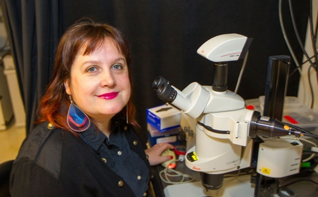 Woman sitting in front of a microscope