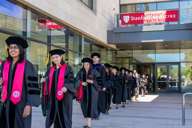 Students in caps and gowns walking out of a building under a Stanford Medicine banner