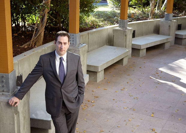 Man in a suit standing in an outdoor courtyard