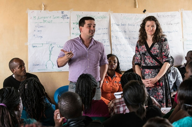 Man and woman talking to a room full of young Kenyan students