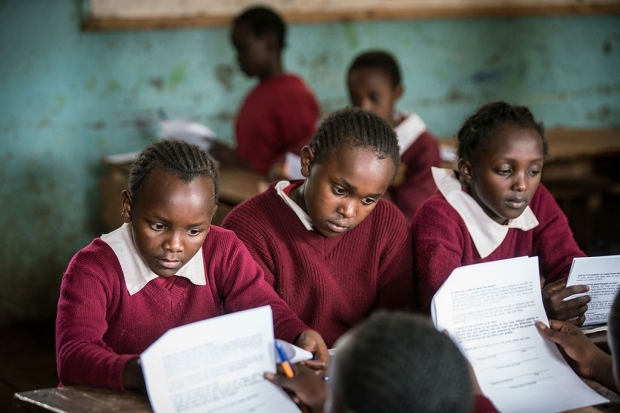 Kenyan girls sitting at a desk while filling out a survey