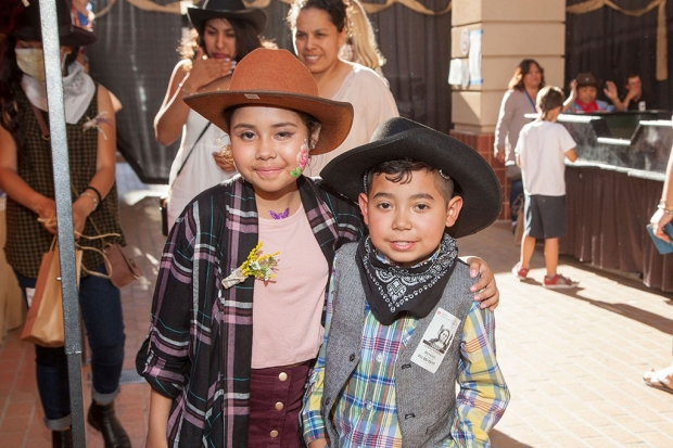 Young girl with her arm around a young boy, both wearing cowboy outfits