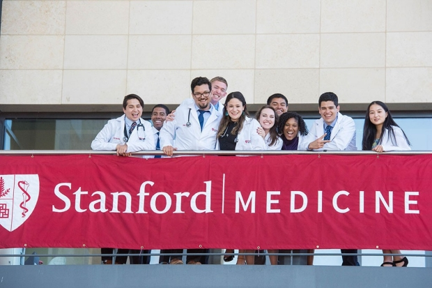 Medical students in white coats standing on a balcony draped with a banner for Stanford Medicine