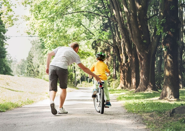 Father helping a child learn to ride a bike