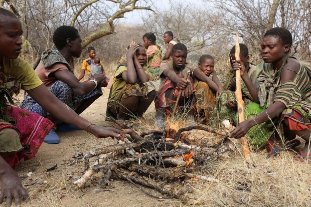 Group of Hadza hunter-gatherers gathered around a fire