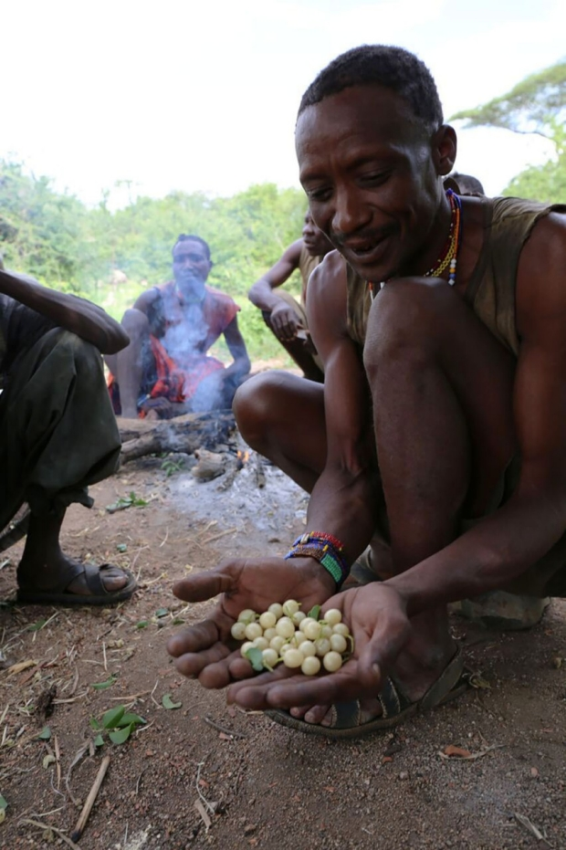 Hadza man holding berries in his hands