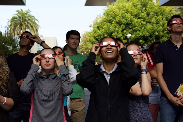 People wearing protective glasses as they look at the sky