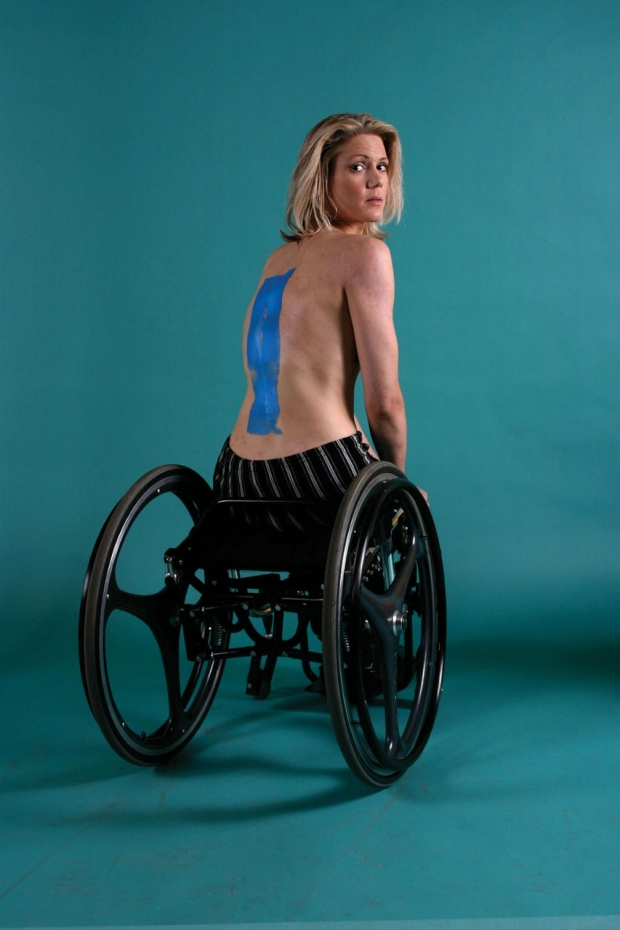 A woman seated in her wheelchair with her back to the camera, showing a blue stripe painted down her spine
