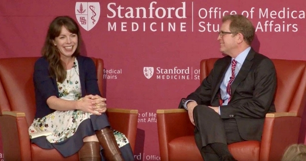 Woman and man seated on a dais at Stanford