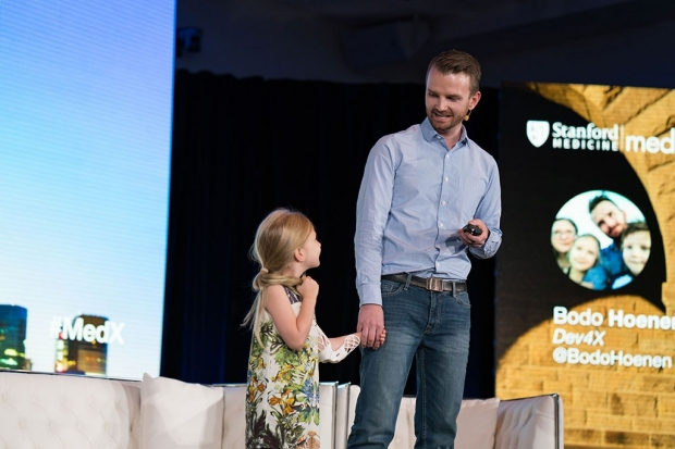Young girl with a brace on her arm holding her father's hand on a stage at a conference