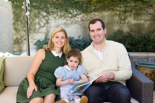 A mother, father and daughter seated on a couch