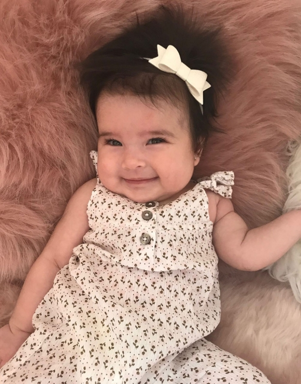 Baby in a dress facing the camera
