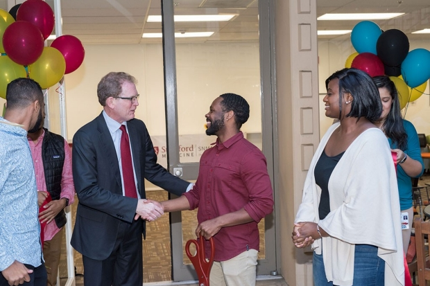 Man shaking hands with another man with balloons in the background