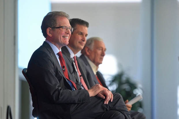 Three men seated on a dais
