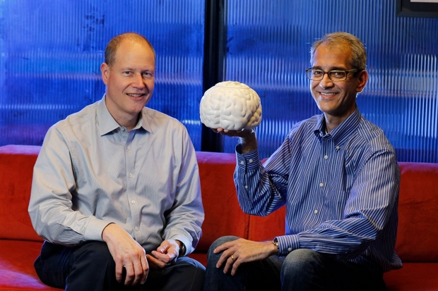 Two men seated on a couch with one of them holding up a model of a brain