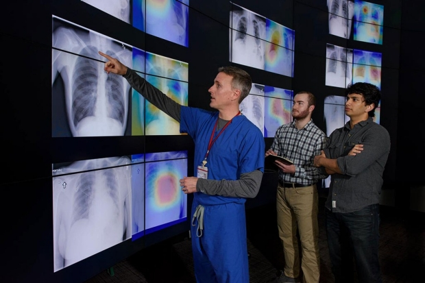 Man in blue scrubs pointing up at a wall of chest X-ray images while two other men look on
