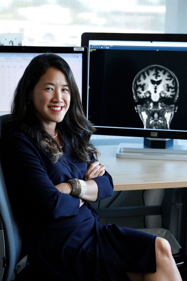 Woman sitting in front of a table holding a monitor displaying an X-ray image of a head