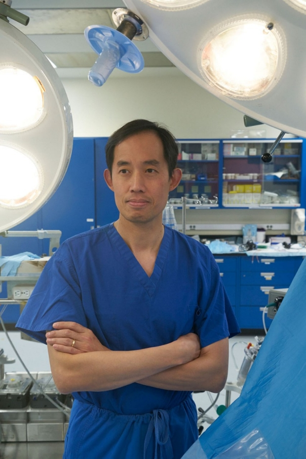 Man in blue scrubs standing in an operating room