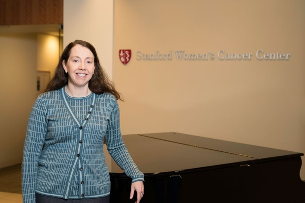 Woman standing in front of a desk at the Stanford Women's Cancer Center
