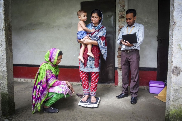 Woman holding a child and standing on a scale while a man and woman watch