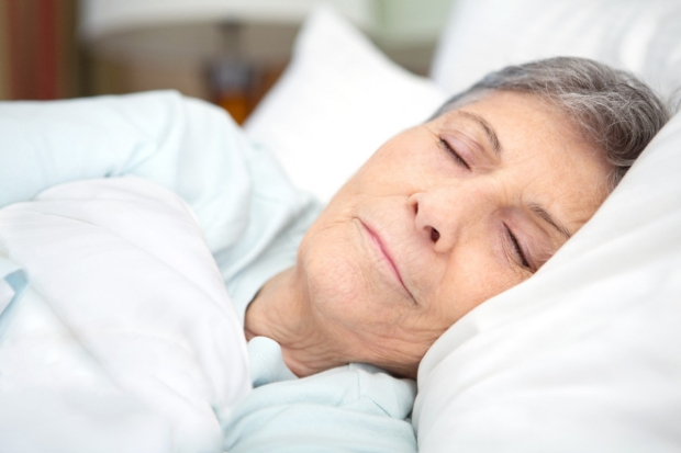 Older woman asleep in a bed