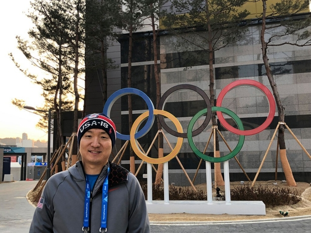 Man standing in front of Olympic rings