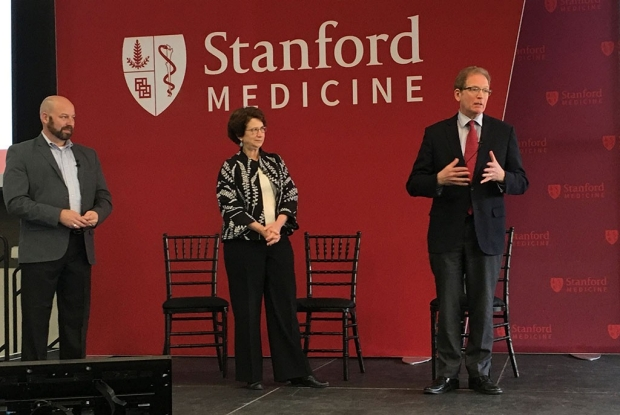 Samuel Zelch, Marcia Cohen and Lloyd Minor stand on a stage
