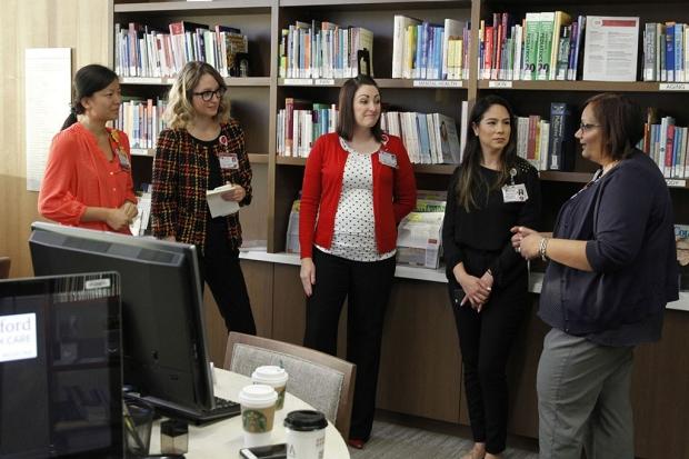 Five women standing in front of bookshelves