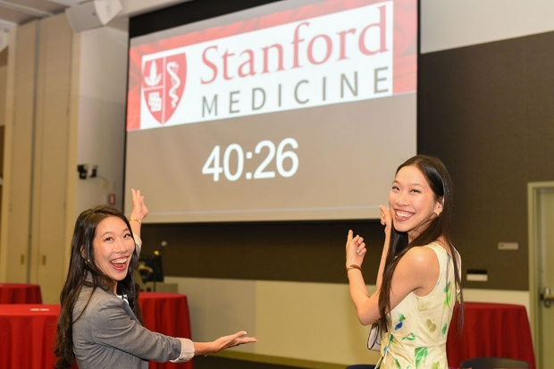 Twin medical students point to the countdown clock for Match Day