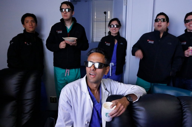 Five people wearing virtual-reality glasses and looking at a screen