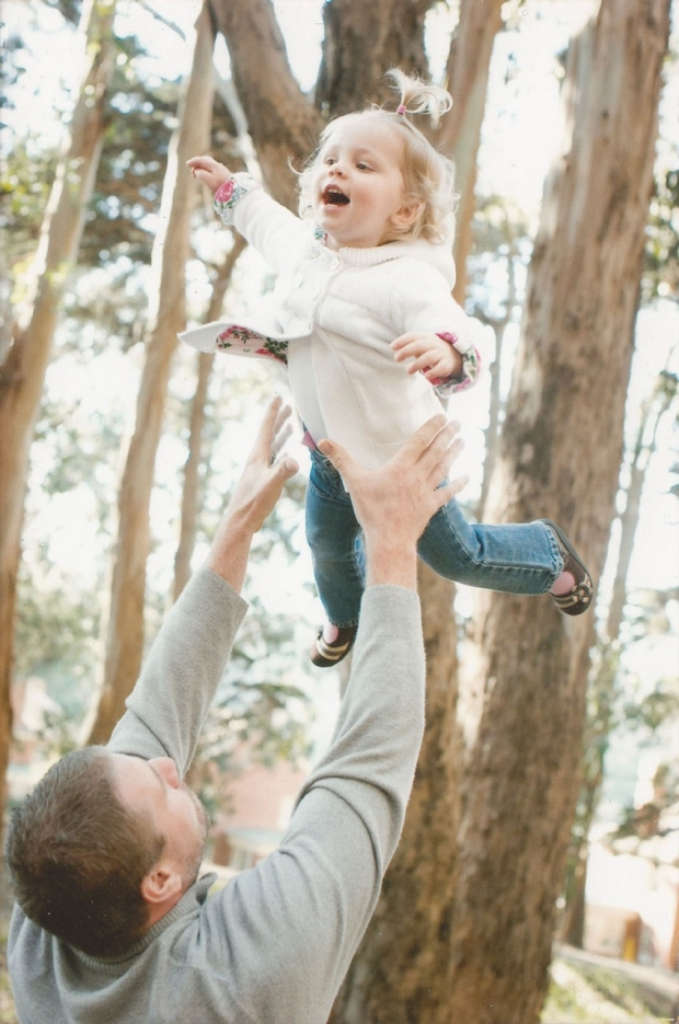 Father tossing Gracin Powell into the air