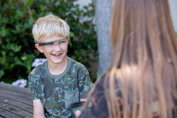 A young boy wearing Google Glass