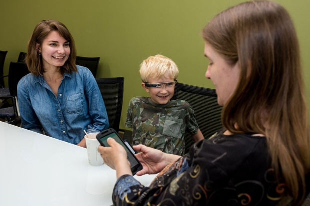 Two women sit at a table with a boy wearing Google Glass
