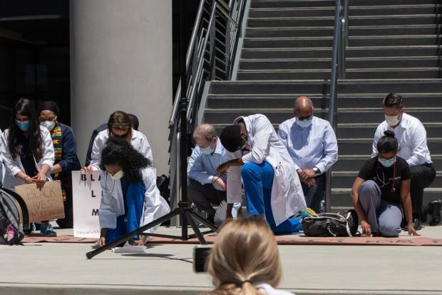 Rally-goers kneel in silence