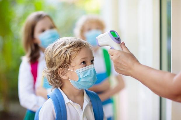 stock photo shows child having temperature checked