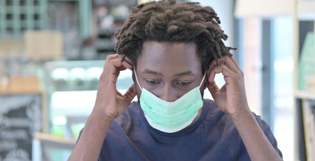 still image showing man putting on mask