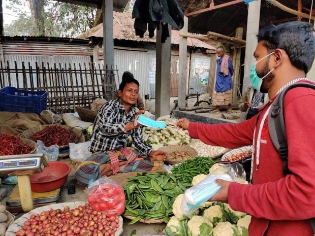 Providing a woman with a surgical mask at a market in Bangladesh