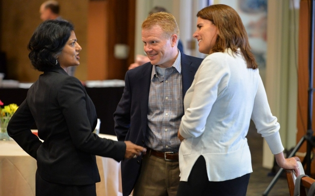 Three faculty members (two women and one man) engaged in conversation