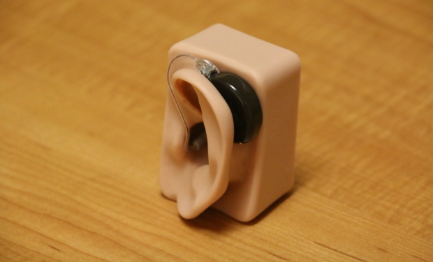photo of a hearing device mounted on a plastic ear