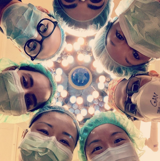 Surgeons in scrubs standing in circle all looking down