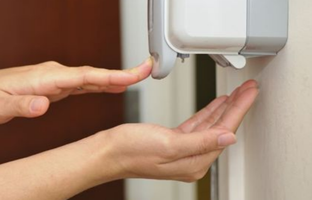 Hands using a hand sanitizer dispenser